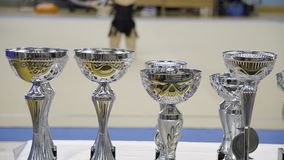 Tazze dei premi, ginnastica ritmica, prestazione vaga dell'atleta nei precedenti stock footage