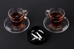 Tazze del portacenere del nero e del tè con le sigarette Fotografie Stock