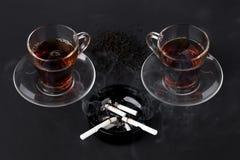 Tazze del portacenere del nero e del tè con le sigarette Fotografie Stock Libere da Diritti