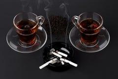 Tazze del portacenere del nero e del tè con le sigarette Fotografia Stock