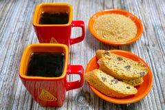 Tazze del primo piano con il caffè del caffè espresso, lo zucchero bruno crudo e il amandel c Immagini Stock