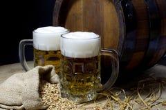 Tazze della borsa della birra, del barilotto e della iuta riempita di grano sulla Tabella di legno contro fondo nero Fotografia Stock Libera da Diritti