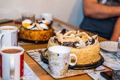 Tazze delle tazze di tè con due crostate del dolce del dessert sulla tavola di legno a casa Fotografia Stock Libera da Diritti