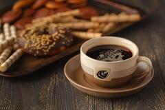 Tazze delle guarnizioni di gomma piuma del cioccolato e del tè su un fondo nero Fotografia Stock