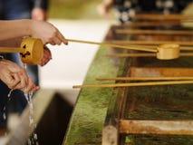 Tazze di bambù dell'acqua di legno del merlo acquaiolo utilizzate per la purificazione degli ospiti Immagine Stock