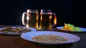 Tazze di birra con la birra della schiuma su un fondo nero su una tavola di legno con gli spuntini a colori la luce video d archivio