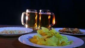 Tazze di birra con la birra della schiuma su un fondo nero su una tavola di legno con gli spuntini archivi video