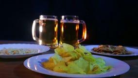 Tazze di birra con la birra della schiuma su un fondo nero su una tavola di legno con gli spuntini video d archivio