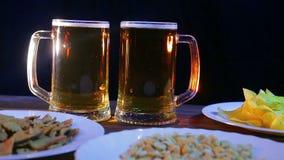 Tazze di birra con la birra della schiuma su un fondo nero su una tavola di legno con gli spuntini stock footage