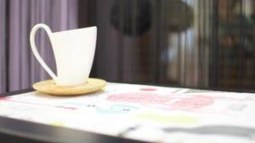 tazze di caffè bianche su un fondo delle tende nere sulla tavola stock footage