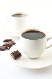 Tazze di caffè con cioccolato ed i piattini su bianco Immagine Stock Libera da Diritti