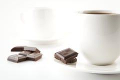 Tazze di caffè con cioccolato ed i piattini su bianco Immagini Stock Libere da Diritti