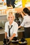 Tazze di caffè del servizio della cameriera di bar che fanno la donna del caffè espresso Immagini Stock Libere da Diritti