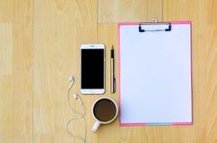 Tazze di caffè del telefono del modello, carta per appunti delle cuffie disposta su una vista superiore di legno fotografia stock libera da diritti