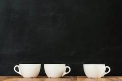 Tazze di caffè macchiato ceramiche raggruppate sul pavimento di legno Immagine Stock