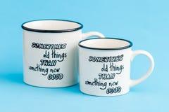 Tazze di caffè macchiato creative e sveglie su fondo blu Fotografie Stock
