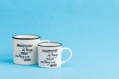 Tazze di caffè macchiato creative e sveglie su fondo blu Fotografia Stock