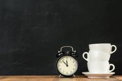 Tazze di caffè macchiato impilate con la retro sveglia Fotografia Stock