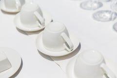 Tazze di caffè macchiato sottosopra sui piattini Fotografia Stock