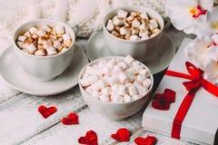Tazze di caffè o di cacao caldo con le caramelle gommosa e molle e la cannella, contenitore di regalo Immagine Stock
