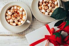 Tazze di caffè o di cacao caldo con le caramelle gommosa e molle e la cannella, contenitore di regalo Fotografie Stock Libere da Diritti