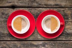 Tazze di caffè piene a metà e vuote a metà su fondo di legno Fotografia Stock