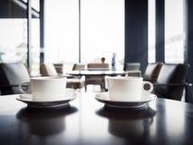 Tazze di caffè sulla tavola con la gente vaga in caffè del negozio del ristorante Fotografie Stock