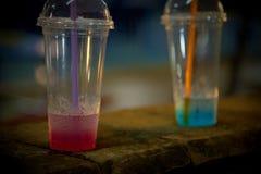 Tazze di plastica con acqua colorata interna e una gocciolina fuori Fotografia Stock