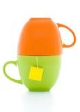 Tazze di tè arancione e verde con la bustina di tè Immagine Stock