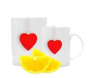 Tazze di tè bianche con le fette rosse del limone e del tealabel isolate su wh Immagini Stock Libere da Diritti