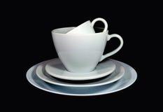 Tazze di tè bianche su accatastate della porcellana e tazze di caffè con i piattini nella dimensione differente Fotografia Stock