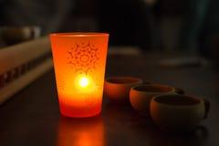 Tazze di tè cinesi e candela aromatica nello scuro Immagini Stock Libere da Diritti