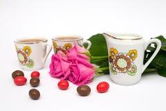 Tazze di tè, delle caramelle e delle rose Immagine Stock
