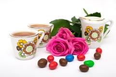Tazze di tè, delle caramelle e delle rose Fotografie Stock