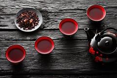 Tazze di tè e della teiera sulla tavola di legno nera fotografie stock