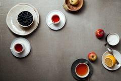 Tazze di tè ed ingredienti di riempimento della torta Immagini Stock