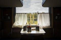 Tazze di tè sulla tavola nel treno immagini stock