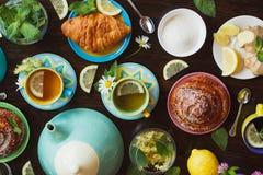 Tazze di tisana con le foglie di menta e del limone, della radice dello zenzero e del croissant sui precedenti di legno, vista su Fotografie Stock