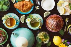 Tazze di tisana con le foglie di menta e del limone, della radice dello zenzero e delle merci al forno sui precedenti di legno Immagine Stock