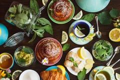Tazze di tisana con le foglie di menta e del limone, della radice dello zenzero e delle merci al forno sui precedenti di legno Fotografia Stock Libera da Diritti