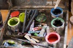 Tazze di vernice, spazzole e matite di carbone di legna Immagini Stock Libere da Diritti