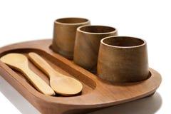 Tazze e cucchiai di legno sul supporto di legno Fotografia Stock