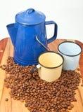 Tazze e fagioli della caldaia del caffè con priorità bassa bianca Fotografie Stock