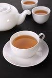 Tazze e vaso di tè sulla tavola fotografia stock