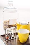 Tazze ed insieme della teiera con gli orologi e tè sciolto in un contenitore su fondo bianco, prodotto per la sala da tè sul piat Fotografia Stock Libera da Diritti