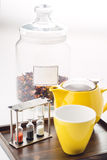 Tazze ed insieme della teiera con gli orologi e tè sciolto in un contenitore su fondo bianco, prodotto per la sala da tè sul piat Immagine Stock Libera da Diritti