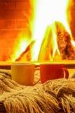 Tazze per tè con la sciarpa della lana contro il camino accogliente Fotografia Stock Libera da Diritti