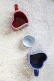 Tazze rosse e blu nella forma di cuore e di piccolo quello bianco Immagini Stock