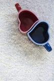 Tazze rosse e blu nella forma di cuore sulla pelliccia bianca Fotografia Stock