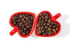 Tazze rosse sotto forma di cuori con i chicchi di caffè su bianco Fotografie Stock Libere da Diritti